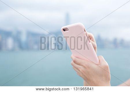 Human hand sending sms on phone