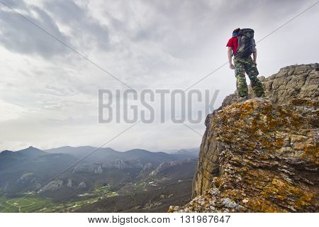 man with backpack standing on a cliff in mountains with green forest and clouds on background