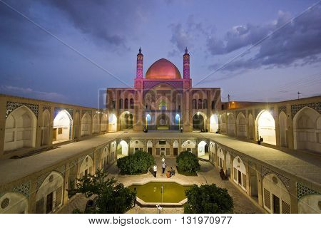 Agha Bozorg school and mosque in Kashan in evening with purple lights on, Iran, with small garden inside