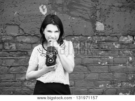 Woman photographer with retro camera in hand on a brick wall background. Girl is thinking and looking at camera. Grayscale photo with copy space.