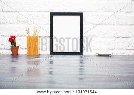 Front view of blank frame pencil holder cactus and saucer on wooden surface and white brick wall background. Mock up