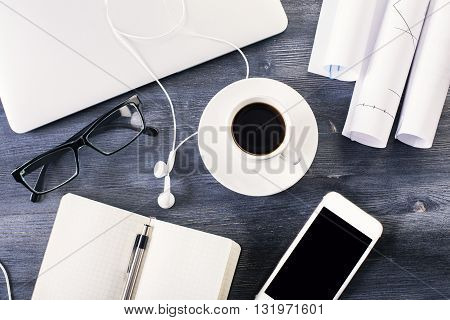 Topview of dark wooden office desk with coffee closed laptop headphones glasses smartphone and other items