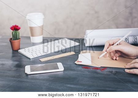 Side view of female's hand writing on paper placed on wooden desktop with smart phone coffee cup computer keyboard cactus and other items. Mock up