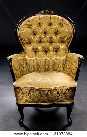 Vintage chair on short legs mustard color beautiful material, texture, wood. Studio, black background., button material