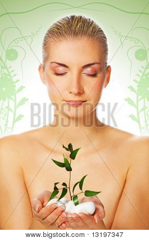 Beautiful blond girl holding young plant growing up through stones on abstract background