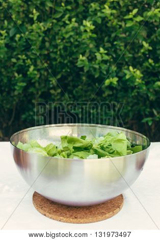 Fresh mixed green salad in bowl on wooden table