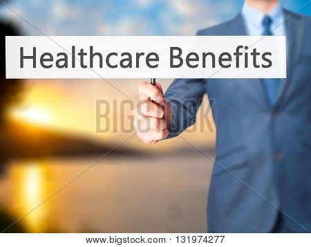 Healthcare Benefits - Businessman Hand Holding Sign