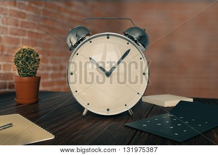 Glossy alarm clock on wooden desktop with cactus calculator and other items on red brick wall background. 3D Rendering