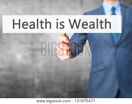Health Is Wealth - Businessman Hand Holding Sign