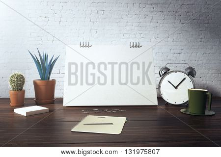 Closeup of desktop with blank card plants coffee cup alarm clock and stationery items on white brick background. Mock up 3D Rendering