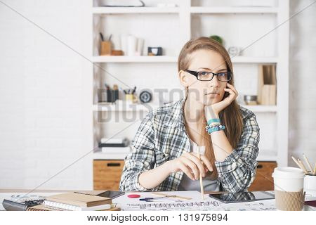 Pretty caucasian girl resting her chin on hand at office desk