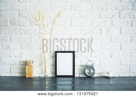 Blank picture frame on wooden desktop with pencil holder wheat spikes alarm clock and coffee cup on white brick wall backgroud. Mock up