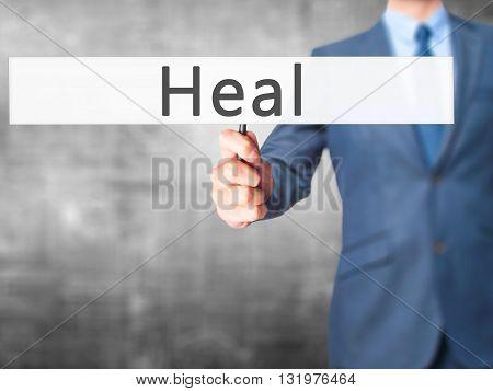 Heal - Businessman Hand Holding Sign