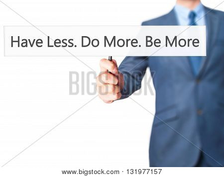 Have Less. Do More. Be More - Businessman Hand Holding Sign