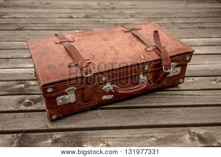 Brown vintage leather suitcase on a wooden deck lying flat viewed high angle in a travel concept
