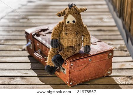 Single cute toy horse sitting in relaxed manner on suitcase over wooden deck outdoors