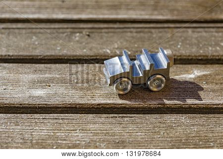Close up on tiny die cast metal toy open top car on brightly lit wooden deck with copy space