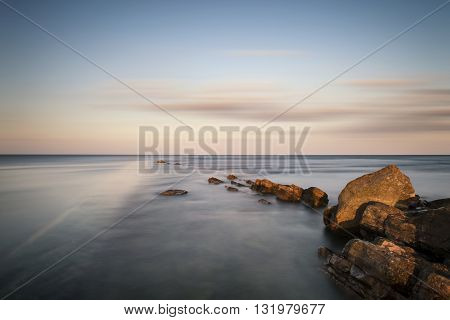 Stunning Long Exposure Landscape Of Sea Over Rocks At Sunset