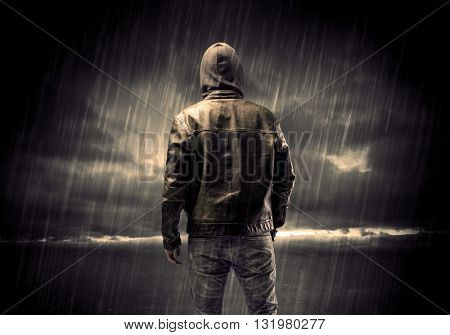 A faceless thief in unrecognizable hoodie standing in the middle of the night in the rain in front of landscape concept