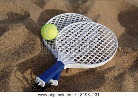 Beach tennis rackets and ball on sand