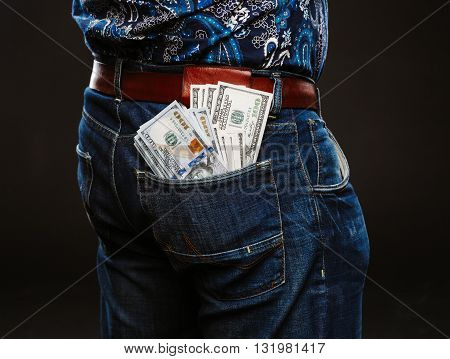 A man holding a lot of money. Banknotes of 100 dollars in different pockets, the concept of corruption