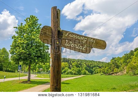 Wooden signpost labeld with footpath to the Wental valley (Fussweg ins Wental)