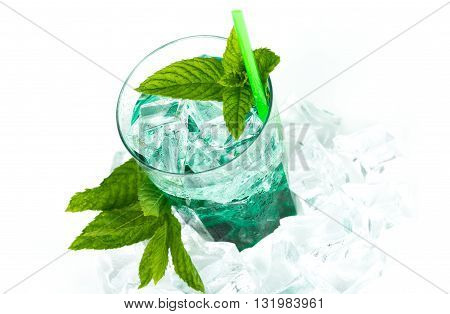 Iced green peppermint syrup with tonic water and ice cubes. Isolated on white background.