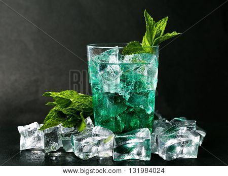 Iced green peppermint syrup with tonic water and ice cubes