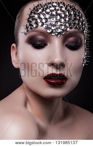 close-up portrait of a beautiful girl with bright makeup and spikes on his face on a black background. Red lips. metal spikes. beautiful eyes.