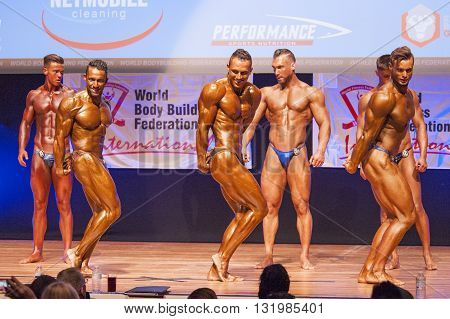 MAASTRICHT THE NETHERLANDS - OCTOBER 25 2015: Male bodybuilders Ali Rezah from Iran with other competitors flex their muscles and show their best physique in a triceps pose on stage at the World Grandprix Bodybuilding and Fitness