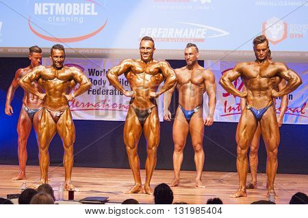 MAASTRICHT THE NETHERLANDS - OCTOBER 25 2015: Male bodybuilders Ali Rezah from Iran with other competitors flex their muscles and show their best physique in a front lats spread pose on stage at the World Grandprix Bodybuilding and Fitness