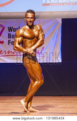 MAASTRICHT THE NETHERLANDS - OCTOBER 25 2015: Male bodybuilder flexes his muscles and shows his best physique in chest front pose on stage at the World Grandprix Bodybuilding and Fitness of the WBBF-WFF