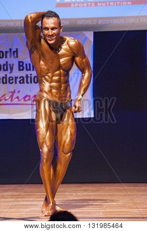 MAASTRICHT THE NETHERLANDS - OCTOBER 25 2015: Male bodybuilder Ali Rezah from Iran flexes his muscles and shows his best physique in a abdominal and thighs pose on stage at the World Grandprix Bodybuilding and Fitness