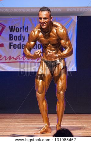 MAASTRICHT THE NETHERLANDS - OCTOBER 25 2015: Male bodybuilder Ali Rezah from Iran flexes his muscles and shows his best physique in a most muscularpose on stage at the World Grandprix Bodybuilding and Fitness
