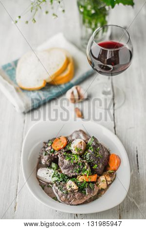 Beef bourguignon in a white ceramic plate with a glass of wine vertical