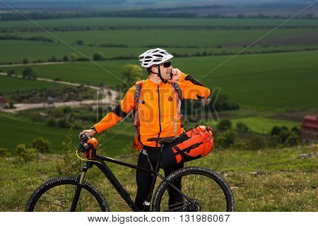 Young man cyclist standing near the cycle on a green meadow and talking the phone