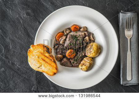 Beef bourguignon in a ceramic plate with grilled potatoes and fork horizontal