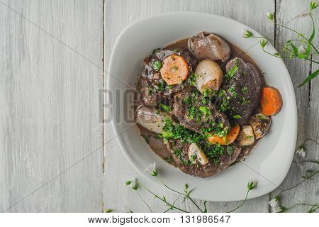 Beef bourguignon in ceramic plate on white boards horizontal