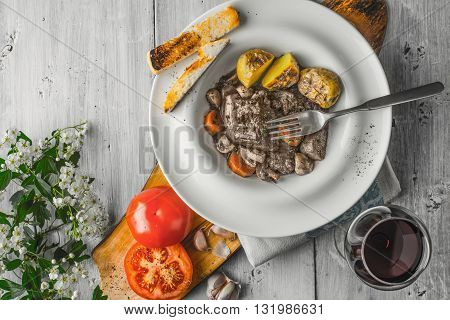 Beef bourguignon in a ceramic plate red wine and white flowers horizontal