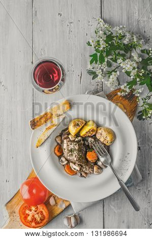 Beef bourguignon in a ceramic plate red wine and white flowers vertical
