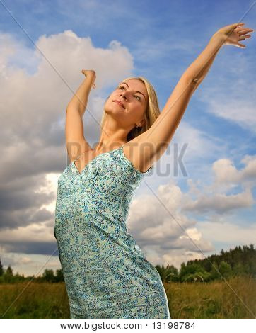 Pretty young woman over blue cloudy sky