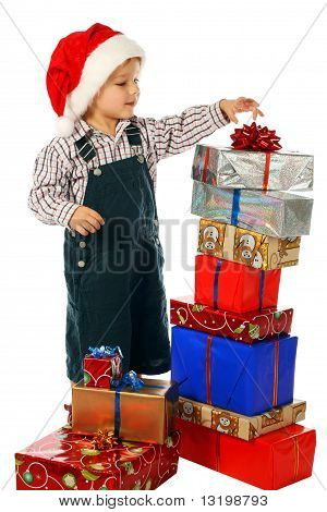 Smiling little boy with lot Christmas gift boxes