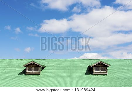 Green roof with two windows against blue sky and clouds