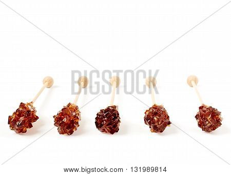 Five brown sugar stirrers isolated on white