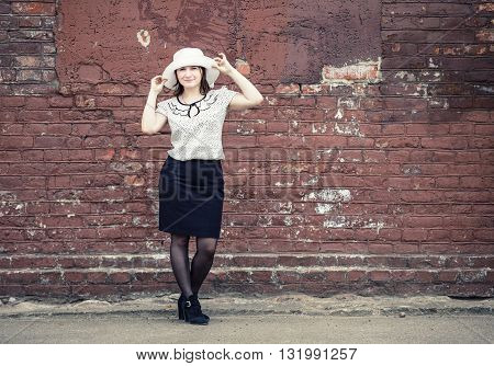 Pretty young woman in white hat blouse and black skirt standing against brick wall background. Girl holds the edges of the hat by hands. Toned photo with copy space. Vintage style photo.