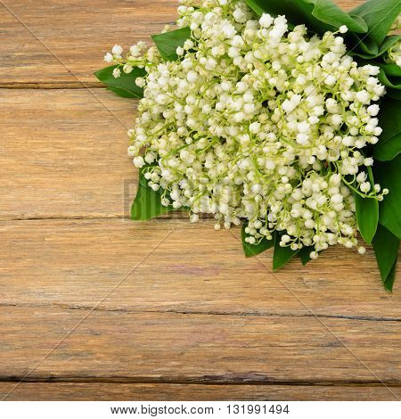Bouquet lily of the valley on wooden table. Spring flowers on old wooden background. Top view.
