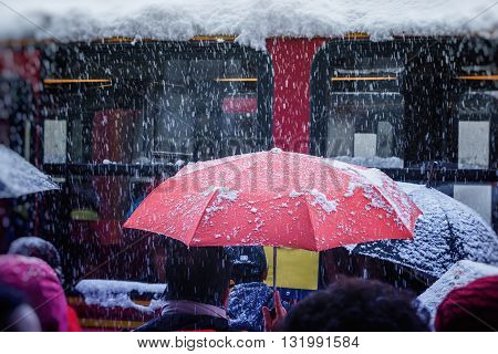 People with red umbrella waiting for train in snowstorm transportation in winter with snow
