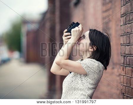 Pretty young woman taking photo outdoors. Girl holding vintage camera and taking photographs. Retro style photo. Selective focus on woman. Toned photo with copy space.