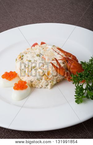 Russian white salad with caviar and crayfish