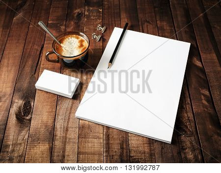 Blank paperwork template: letterhead coffee cup and pencil on vintage wooden table background. Mock-up for ID. Blank stationery template for design portfolios. Top view.